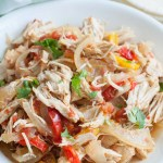 Bowl with shredded chicken, onions and peppers.