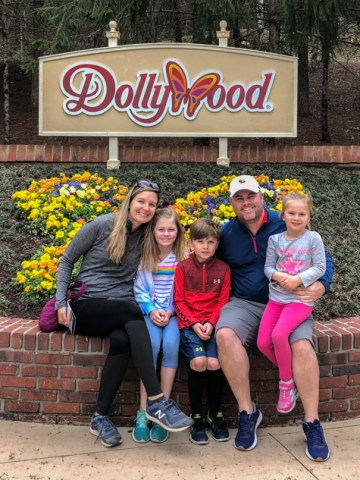 Family sitting in front of Dollywood sign.