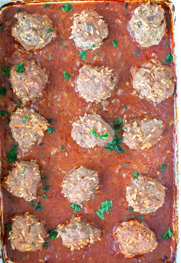 Baked meatballs out of the oven in casserole dish.