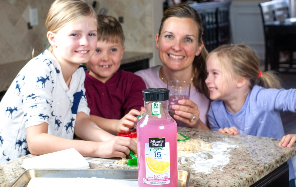Women, boy and two girls with bottle of lemonade.