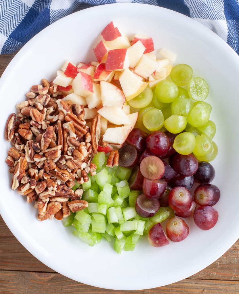 Waldorf Salad ingredients, apples, pecans, grapes, celery in a bowl