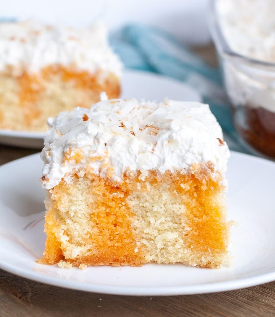 Piece of orange poke cake on a plate