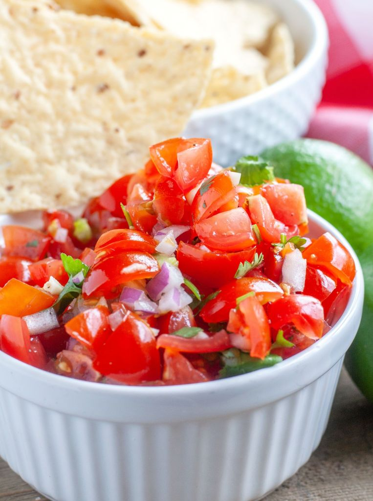 Pico De Gallo In a white bowl with a chip and limes