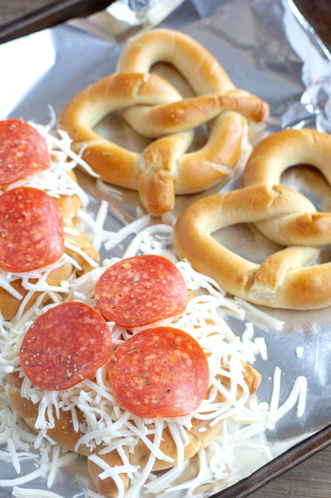 Soft pretzels on foil with pepperoni and cheese.