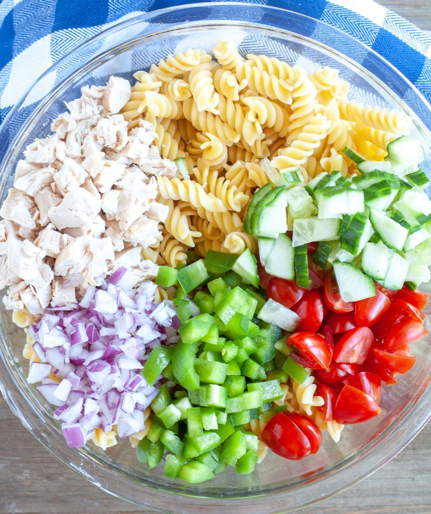 Large Bowl with Pasta, diced chicken, red onion, green pepper, cucumber and diced tomatoes.