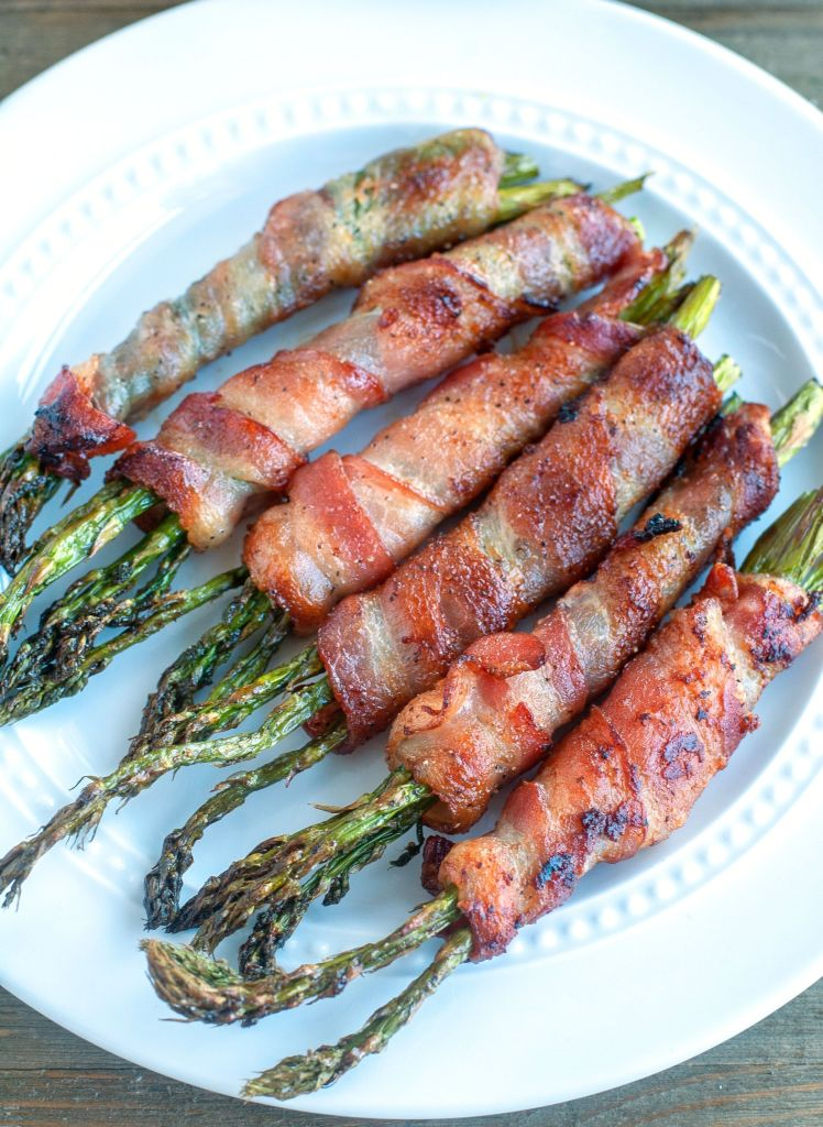 Bacon wrapped asparagus on a white plate