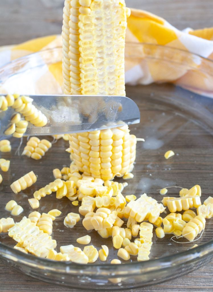 Ear of corn standing in a pie plate with knife cutting off corn kernels