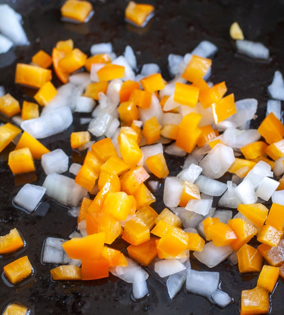 Diced onion and orange bell pepper in a skillet