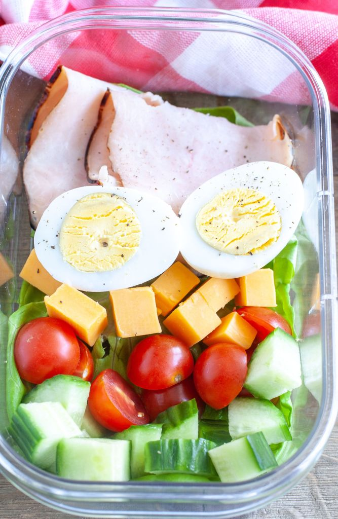 Meal prep container filled with turkey, hard boiled egg, cheese, tomato and cucumber