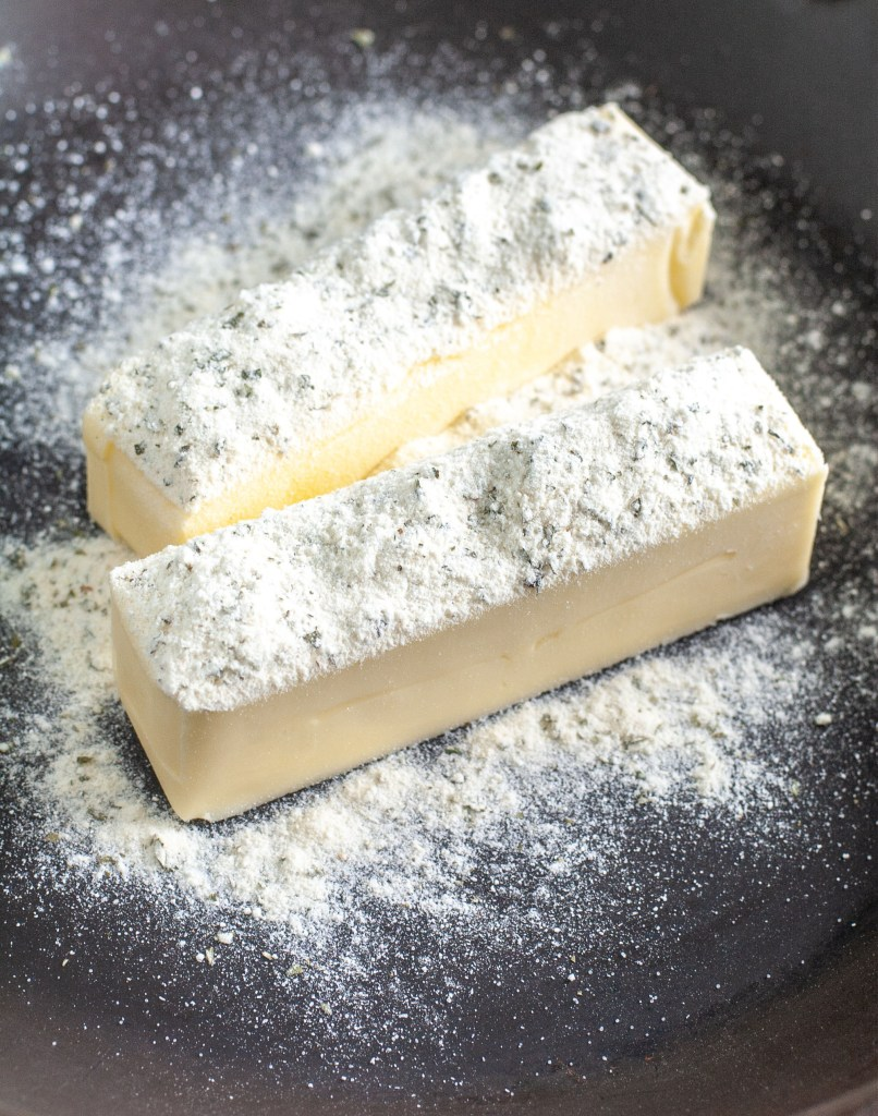 Two sticks of butter in a skillet with ranch seasoning.