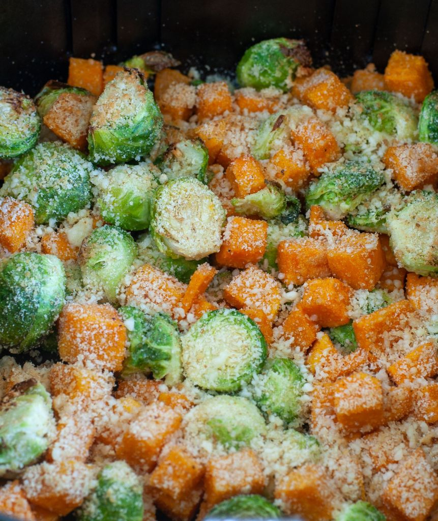 Air fryer basket full of roasted Parmesan brussels sprouts and squash