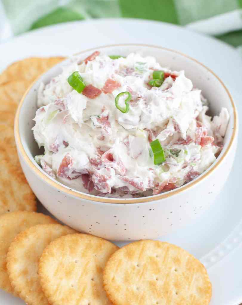 A white plate with a small bowl of chipped beef dip surrounded by crackers