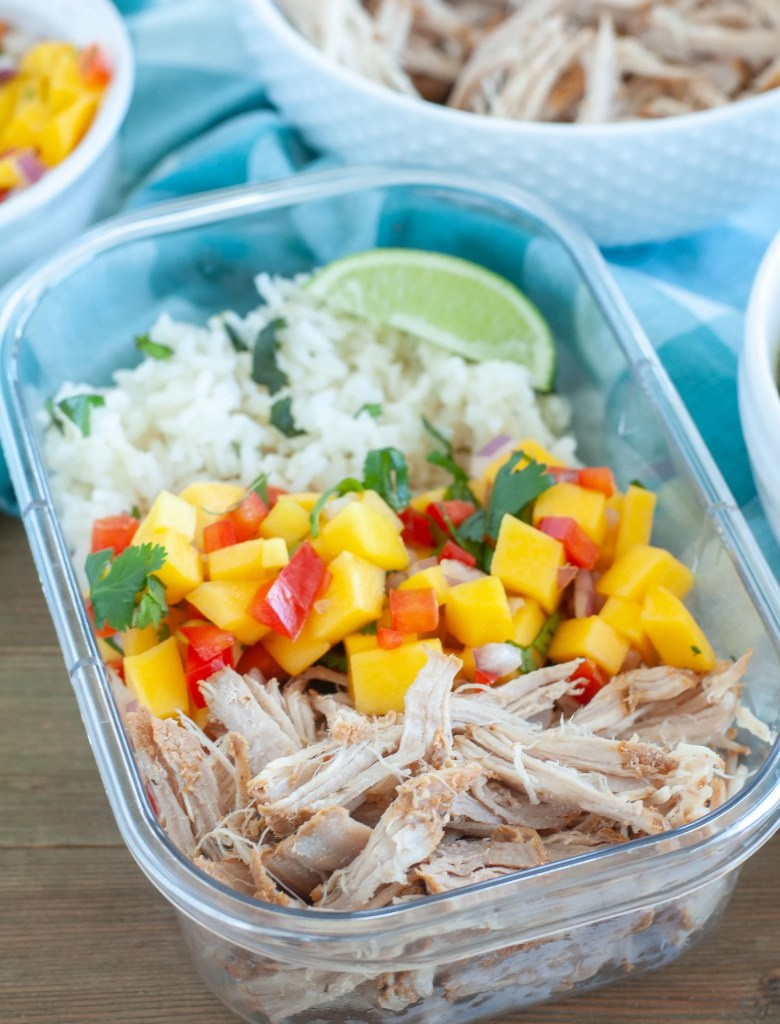 Shredded carnitas, mango salsa and rice in a plastic container