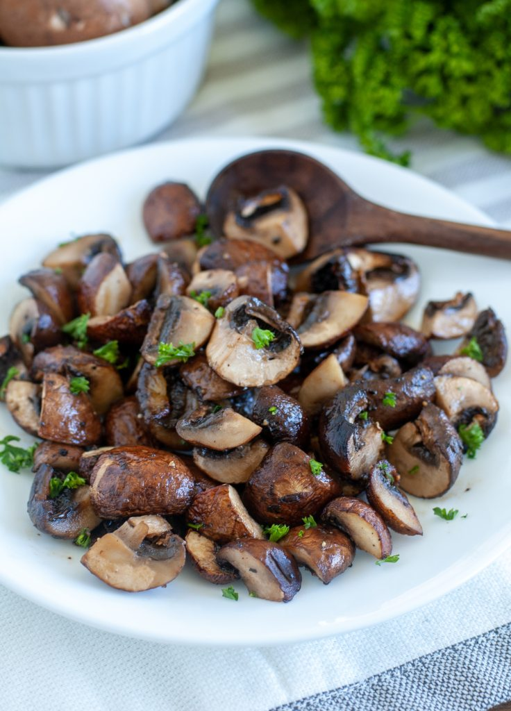 Plate with air fryer roasted mushrooms and small wooden spoon