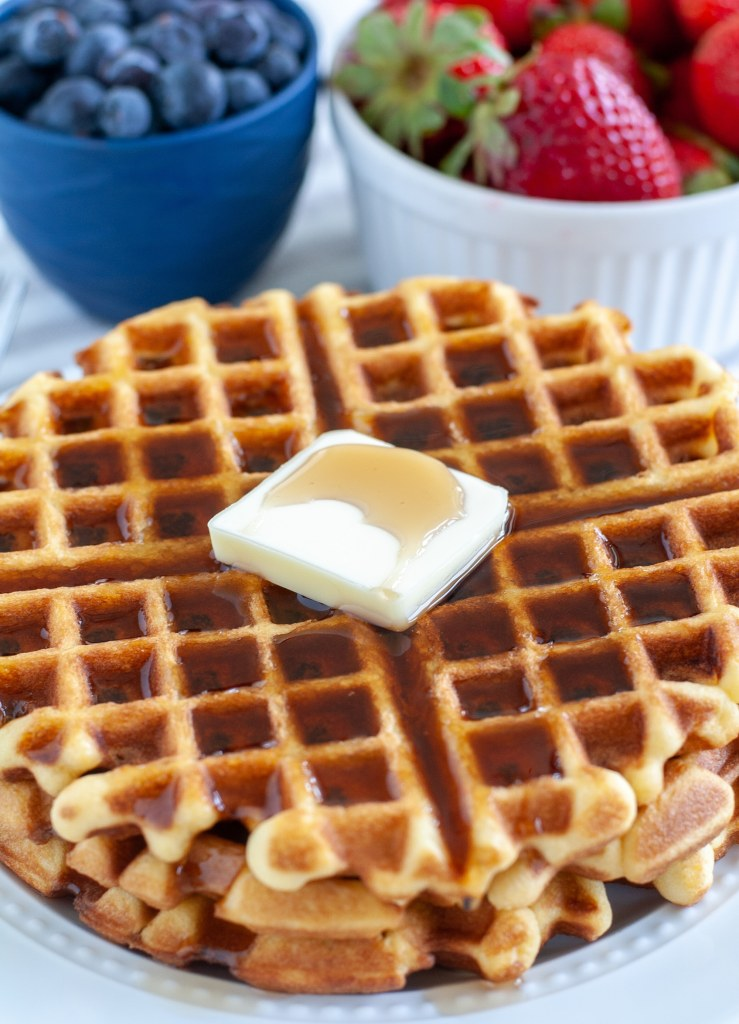 Waffles on a plate with butter and syrup