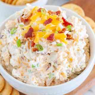 Crack dip in bowl topped with bacon and cheese