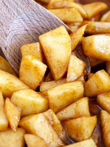 Fried apples with a wooden spoon