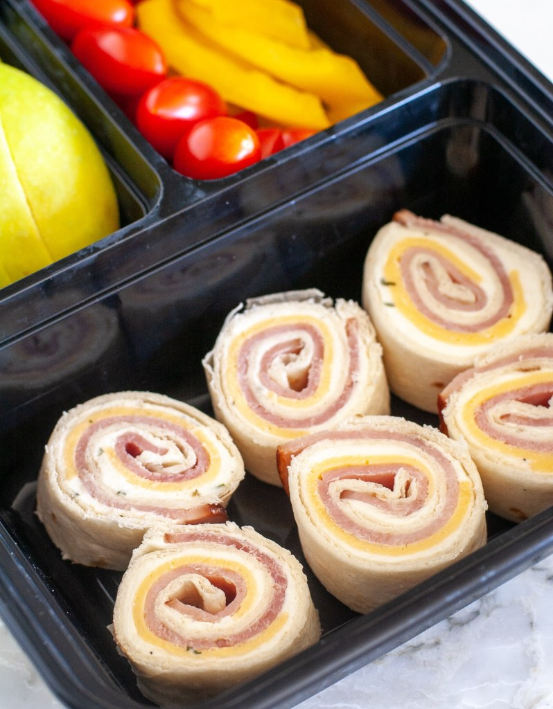 roll ups in box with apple, tomato and peppers