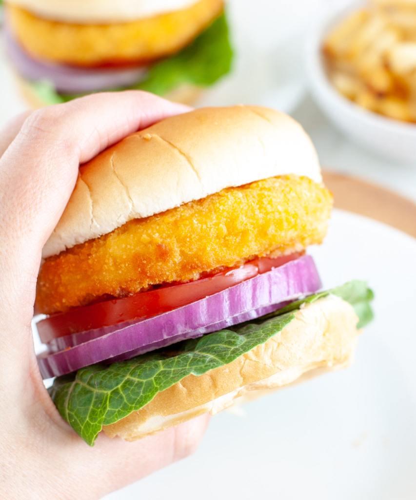 Hand holding chicken sandwich.