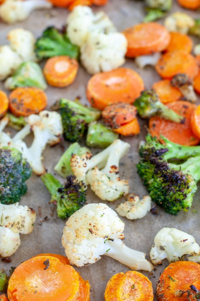 Roasted mixed vegetables on a sheet pan.