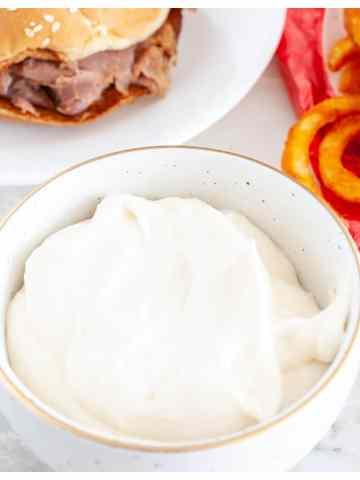 bowl of cream sauce with roast beef sandwich