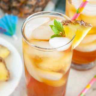 Glass of tea with piece of pineapple.
