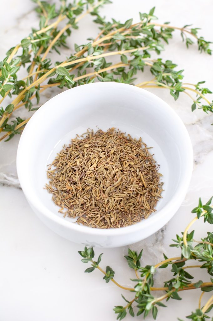 Bowl of dried thyme and fresh thyme.