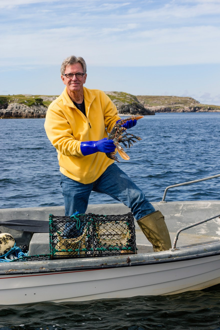Host of Food Over 50, David Jackson holds a fresh caught lobster in Scotland