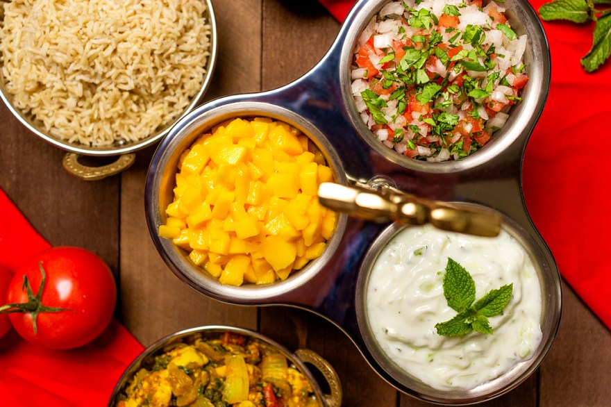 Cucumber raita, mango chutney and onion tomato relish condiments as prepared by Food Over 50