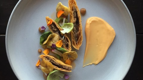 "Chef Jacques La Merde describes this as ""CROSS SECTION OF SPICY BEEF JAMAICAN PATTY, PLAINTAIN CHIPS, ST. HUBERT POUTINE GRAVY FLUID GEL, CHILLY OIL, UTZ MILD CHEDDAR CHEEZE DIP, FROZEN PEAS, LEAFS!!!!"" on his Instagram account."