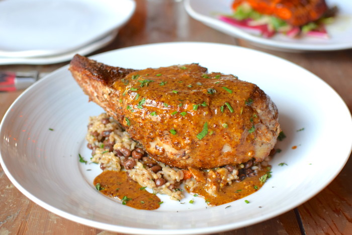 The double cut pork chop at Field & Tides comes smothered in a Creole mustard sauce. (Photo: Mai Pham.)