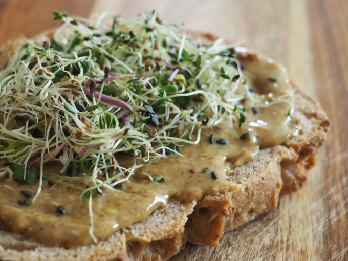 curried almond butter on toast with sprouts