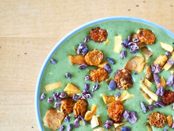 quick and healthy breakfast recipes exotic green smoothie bowl with goldenberries, dried mamgo, and cacao nibs scattered on top