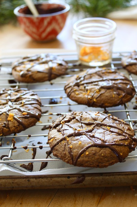 Paleo Flourless Orange Chocolate Gingerbread Cookies on cooling rack with bowl of chocolate and orange zest, backlit