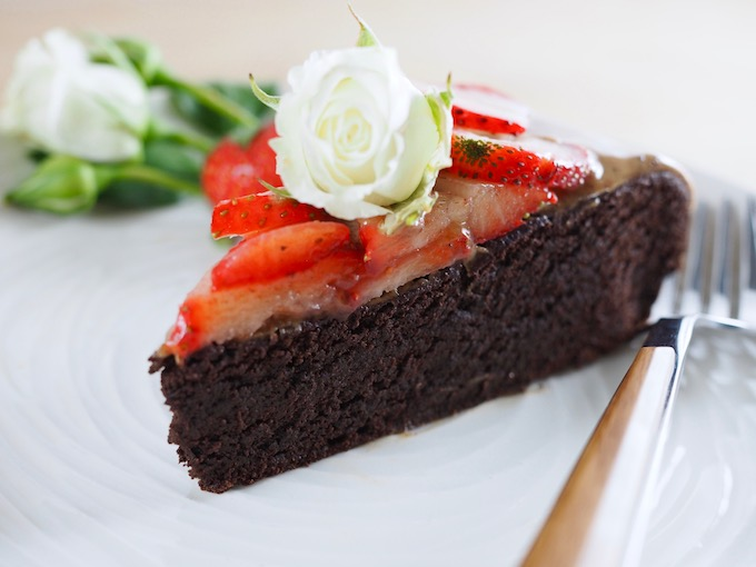 close up on piece of Ultimate Paleo Flourless Chocolate Cake with strawberries on a white plate with fork