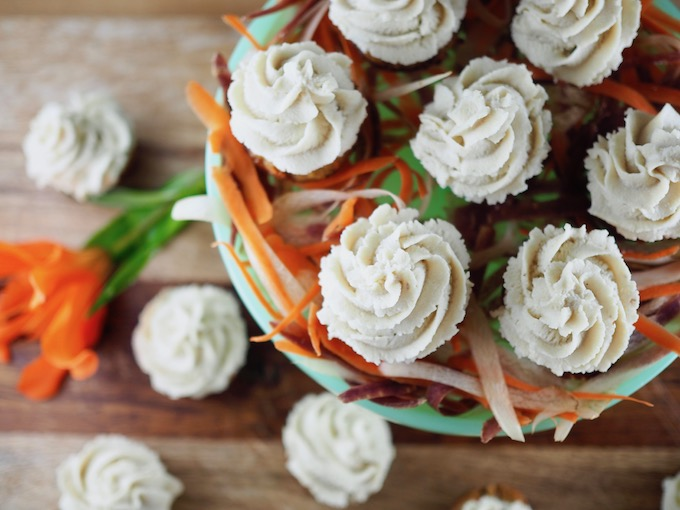 "Mini Coconut Flour Carrot Cake Cupcakes with Honey Vanilla ""Buttercream"" on a blue glass platter with orange lilly"
