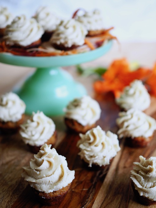 "Mini Coconut FlourCarrot Cake Cupcakes with Honey Vanilla ""Buttercream"" on a blue glass platter on a wooden table"