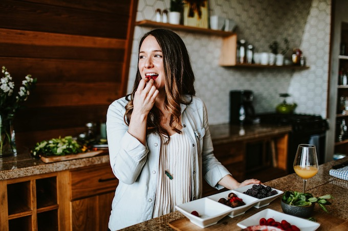 author eating a raspberry with a smile