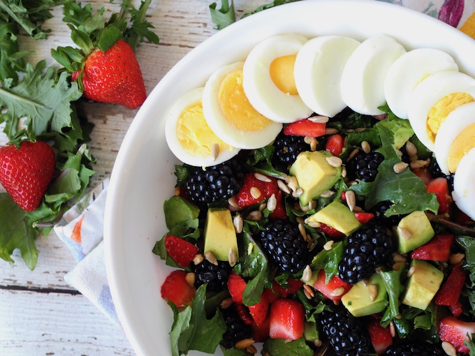 Baby Kale Berry Breakfast Salad on white wooden table with loose strawberries