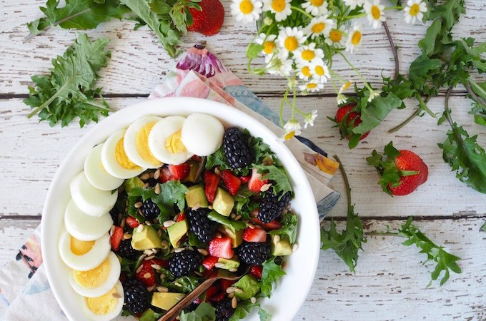 Baby Kale Berry Breakfast Salad on white wooden table with berries and flowers