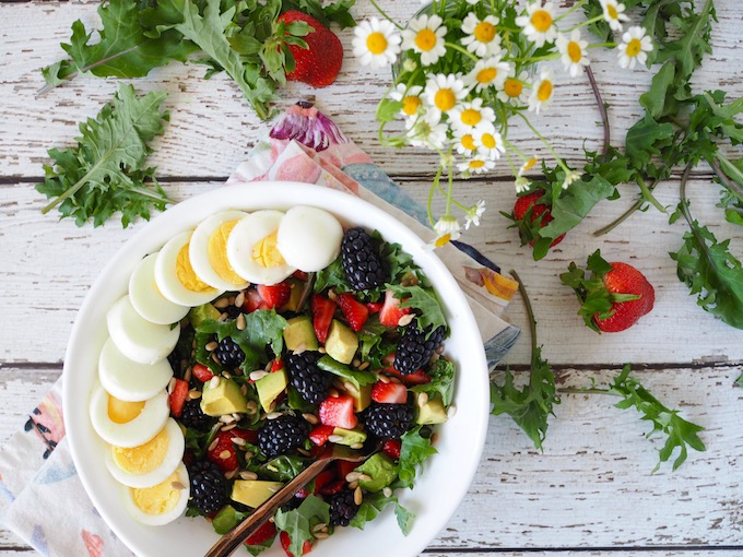 bowl of salad with berries and egg on white wood table with strawberries and flowers