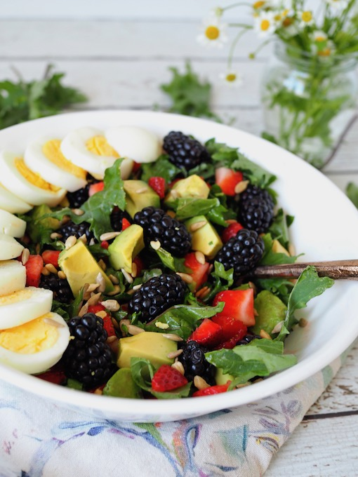 Baby Kale Berry Breakfast Salad in white bowl with fresh flowers in glass jar