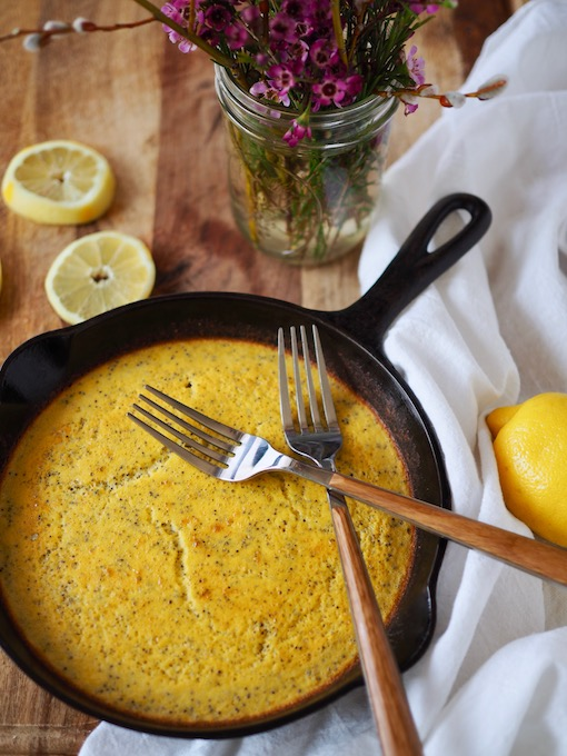 cast iron pan with lemon poppy seed coconut flour bread on wooden table with lemons and flours