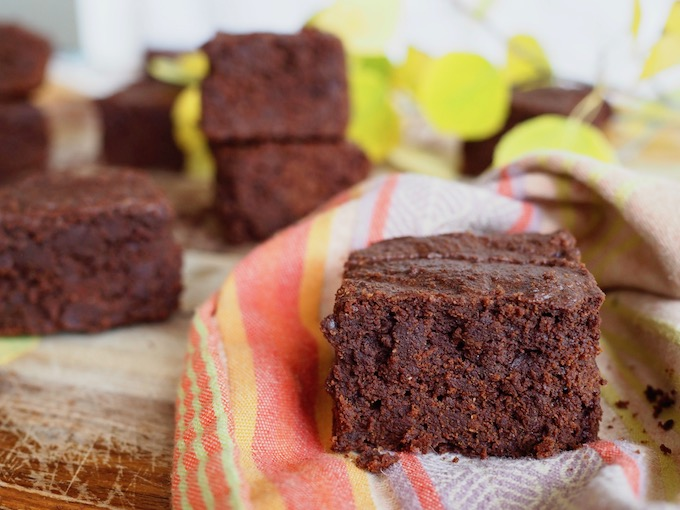 fudgy Tahini Pumpkin Paleo Brownies on orange towel with aspen leaves
