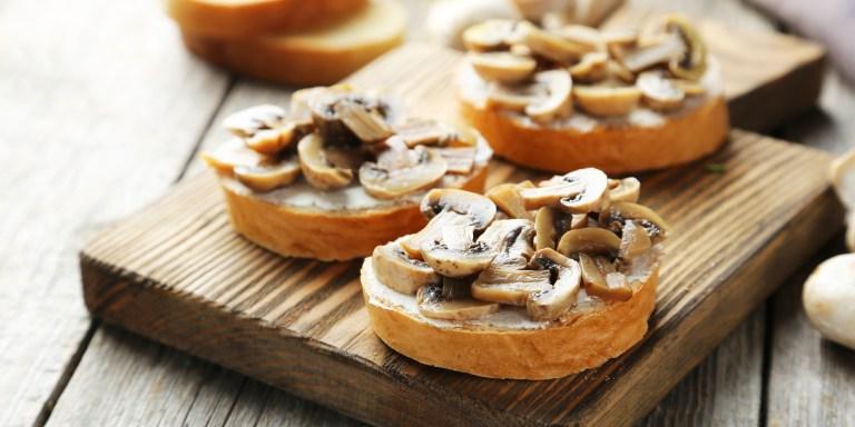 Tasty fresh bruschetta with mushrooms on cutting board on grey w