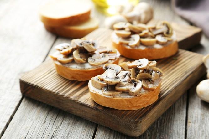 Tasty fresh bruschetta with mushrooms on cutting board on grey wooden background