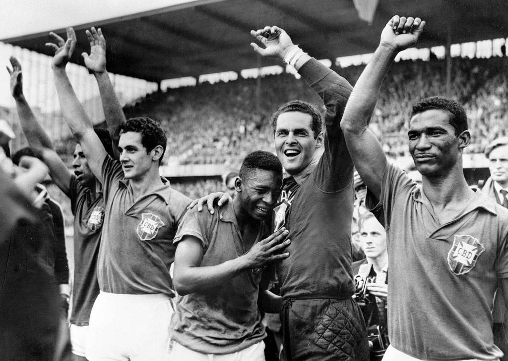 Brazil's 17- year-old star Pele, center, weeps on the shoulder of goalkeeper Gilmar Dos Santos Neves after Brazil's 5-2 victory over Sweden in the final of the World Cup tournament in Stockholm. (l-r) Garrincha, Orlando, Pele, Gilmar and Didi.