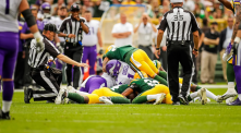 Alan Eck kneels next to the pile as referee John Hussey arrives on the scene. (Green Bay Packers)