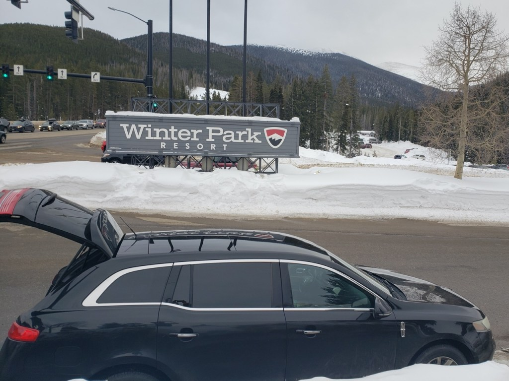 black Lincoln town car arriving at Winter Park