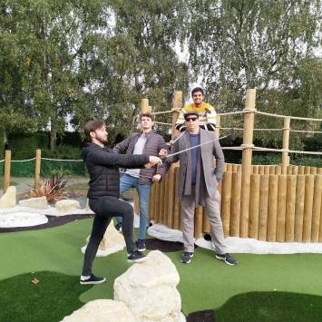 Four men playing miniature golf